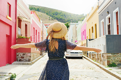 Buy stock photo Rearview shot of an unrecognizable woman walking amongst colourful homes outside