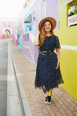 Buy stock photo Shot of a beautiful young woman walking amongst colourful homes outside