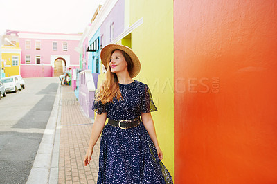 Buy stock photo Cropped shot of a beautiful young woman walking amongst colourful homes outside