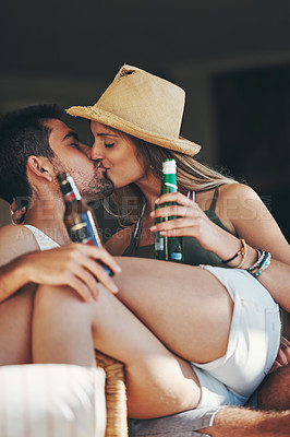 Buy stock photo Cropped shot of an affectionate young couple kissing while enjoying some beers on their patio