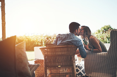 Buy stock photo Rearview shot of an affectionate young couple kissing while enjoying some beers on their patio