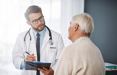 Buy stock photo Cropped shot of a young male doctor going through medical records with his senior male patient