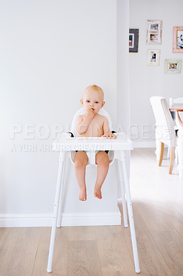 Buy stock photo Portrait of an adorable baby girl sitting in a high chair at home and eating a snack