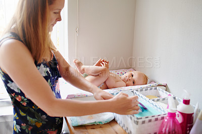 Buy stock photo Portrait of a young woman changing her adorable baby girl's diaper on a table at home