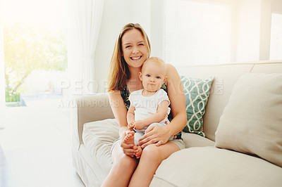Buy stock photo Portrait of a young woman relaxing with her adorable baby girl on the sofa at home