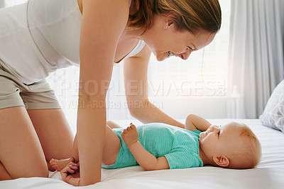 Buy stock photo Shot of an adorable baby girl bonding with her mother on the bed at home
