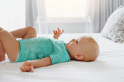 Buy stock photo Shot of an adorable baby girl being lying down on a bed at home