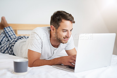 Buy stock photo Shot of a young man using a laptop while having coffee on his bed at home
