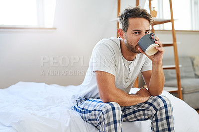 Buy stock photo Shot of a handsome young man drinking coffee in bed at home