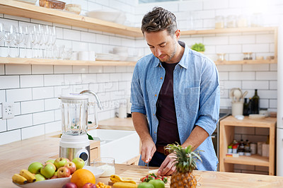 Buy stock photo Shot of a young man making a health smoothie at home