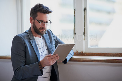 Buy stock photo Cropped shot of a handsome young businessman working on a tablet while standing by his bedroom window