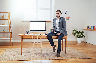 Buy stock photo Cropped portrait of a handsome young businessman working on a tablet while sitting in his home office