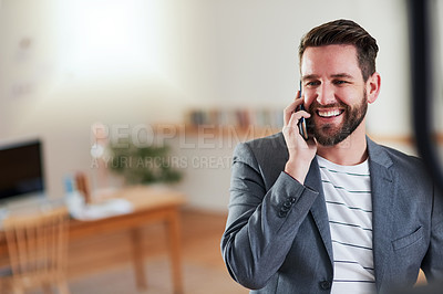 Buy stock photo Cropped shot of a handsome young businessman talking on his cellphone while standing in his home office