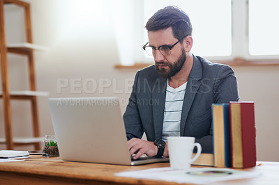Buy stock photo Cropped shot of a handsome young businessman working on his laptop while sitting in the home office