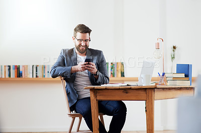Buy stock photo Cropped shot of a handsome young businessman sending a text message while sitting in the home office