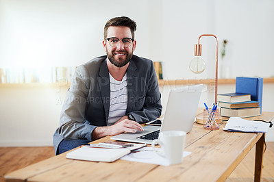 Buy stock photo High angle portrait of a handsome young businessman working on his laptop while sitting in the home office