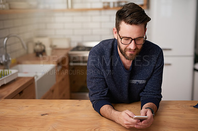 Buy stock photo Cropped shot of a handsome young man sending a text message while standing in the kitchen at home