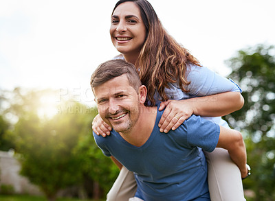 Buy stock photo Shot of a cheerful young man giving his wife a piggyback ride outside in a park during the day