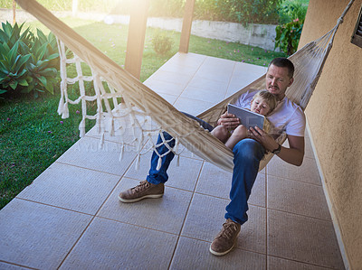 Buy stock photo Shot of a father and his little daughter using a digital tablet while relaxing on a hammock outdoors