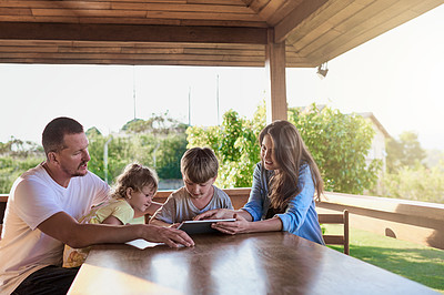 Buy stock photo Shot of a family using a digital tablet together outdoors
