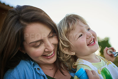 Buy stock photo Shot of a mother and her little daughter blowing bubbles outdoors