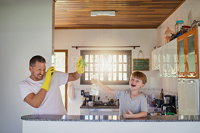 Buy stock photo Shot of a father and his little son having fun while doing chores together at home