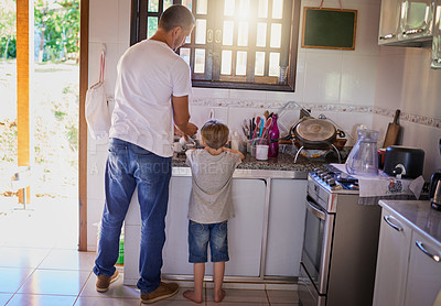 Buy stock photo Rearview shot of a father and his little son washing dishes together at home