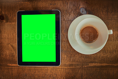 Buy stock photo High angle shot of a digital tablet with a green screen and cup of coffee on a table