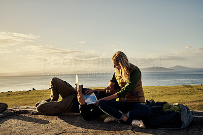 Buy stock photo Shot of an attractive young couple looking at a map for directions together in nature