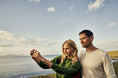 Buy stock photo Cropped shot of an attractive young couple taking photos and spending the day in nature