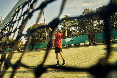 Buy stock photo Low angle shot of a young boy working on his serve during tennis practice