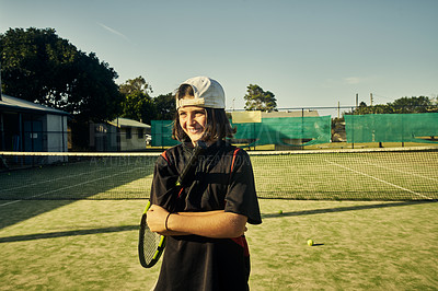 Buy stock photo Cropped shot of a young boy standing with his arms folded on the tennis court