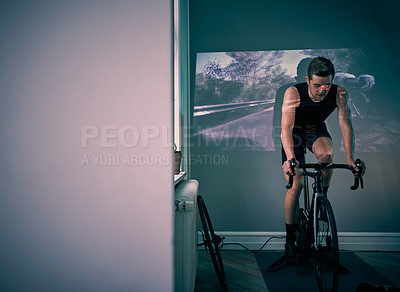Buy stock photo Shot of a young man using a projector while riding an exercise bike at home