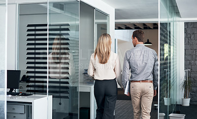 Buy stock photo Rearview shot of two businesspeople walking down a corridor in an office