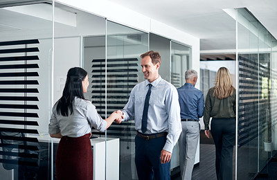 Buy stock photo Shot of businesspeople shaking hands in an office