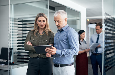 Buy stock photo Shot of two businesspeople using a digital tablet together in an office