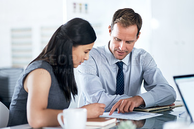 Buy stock photo Shot of a businessman and businesswoman going over paperwork together in a modern office