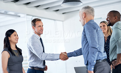Buy stock photo Shot of two businessmen shaking hands during a team meeting in a modern office