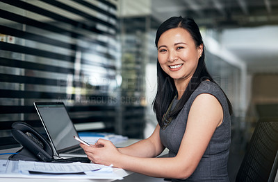 Buy stock photo Portrait of a young businesswoman using a mobile phone at her desk in a modern office