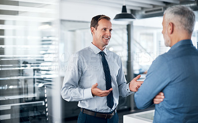 Buy stock photo Shot of two businessmen having a discussion in a modern office
