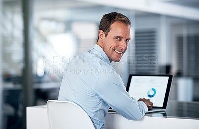 Buy stock photo Portrait of a young businessman using a laptop at his desk in a modern office