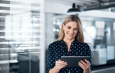 Buy stock photo Shot of a mature businesswoman using a digital tablet in a modern office
