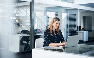 Buy stock photo Shot of a mature businesswoman using a laptop at her desk in a modern office