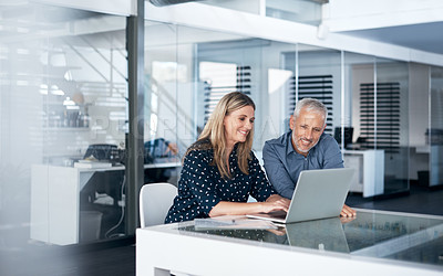 Buy stock photo Shot of a businessman and businesswoman using a laptop together in a modern office