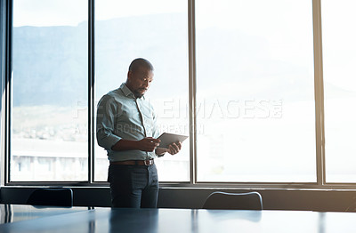 Buy stock photo Shot of a mature businessman using a digital tablet in a modern office