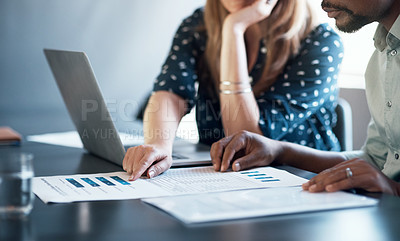 Buy stock photo Cropped shot of a businessman and businesswoman using a laptop while going through paperwork together in a modern office