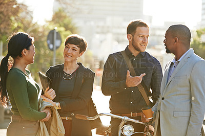 Buy stock photo Cropped shot of four businesspeople chatting while on their way to work