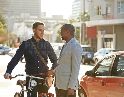 Buy stock photo Cropped shot of two businessmen chatting while on their way to work