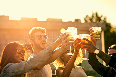 Buy stock photo Cropped shot of a group of young friends having a drink and spending the day outside on a rooftop