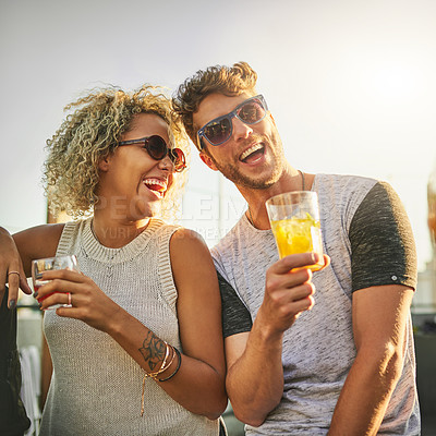 Buy stock photo Cropped shot of an attractive young couple having a drink and spending the day outside on a rooftop